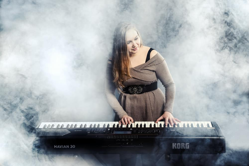 Blonde Frau spielt Piano. Andrea Raffaela Böll spielt auf KORG-Piano.